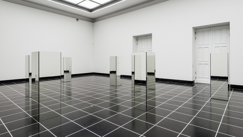 "Adrian Piper, Das Ding-an-sich bin ich, 2018. Eight mirrored Plexiglas cubes, each 180 cm high x 60 wide cm x 60 cm deep (70.86"" x 23.62"" x 23.62""), each housing concealed sound system; eight 8-minute audio files; floor-wide grid of minimum 60 cells each 60 cm x 60 cm (23.62"" x 23.62""), room dimensions variable.  Installation view: Käthe-Kollwitz-Preis 2018. Adrian Piper. Akademie der Künste, Berlin, Sep-Oct 2018. Photo credit: Andreas FranzXaver Süß. Collection Adrian Piper Research Archive Foundation Berlin. © APRA Foundation Berlin."